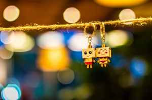 two man and woman wooden couple keychains hanging on rope overlooking bokeh lights