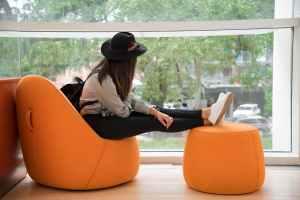 woman sitting on orange chair
