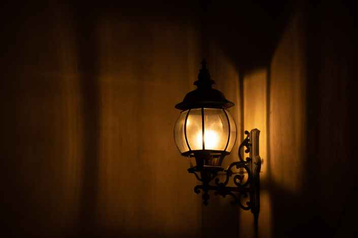 photo of a lighted sconce mounted on a brown wall